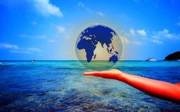 Świat umieszcza na rękach ludzie na morzu obrazy stock