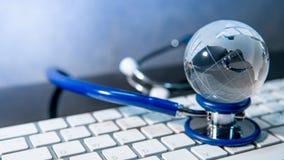 Światowa kula ziemska na stetoskopie i klawiaturze zdjęcie royalty free