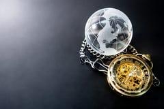 Światowej kuli ziemskiej krystaliczny szkło i kieszeniowy zegarek fotografia stock