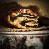 Świeża makowego ziarna rolka na naturalnej bieliźnianej pielusze na nieociosanym drewnianym tle zdjęcia royalty free
