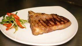 Świeżo gotujący kość stek rozkłada na białym talerzu blisko rozsypiska microgreens Przygotowanie skończony kawałek zdjęcie wideo