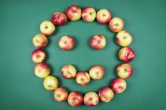 Świezi czerwoni i żółci jabłka tworzy uśmiechniętą twarz na zielonym tle obraz stock