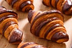 Świezi domowej roboty croissants z czekoladą na drewnie ukazują się zdjęcie royalty free