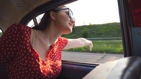 倾斜在减速火箭的车窗外面和享受旅行的太阳镜的愉快的女孩 看窗口移动的少妇老 股票视频