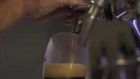 倒黑啤酒的酿酒者对从轻拍的玻璃在啤酒厂 倒壮健啤酒的侍酒者手的关闭对从把柄的玻璃 影视素材