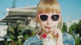 喝奶昔的一个滑稽的女孩的画象在咖啡馆 与儿童概念的休息 股票录像