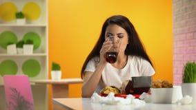 咬住无味的汉堡饮用的苏打水,便宜的食物的女性咖啡馆顾客 股票录像