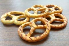 咸酥脆在木桌背景的薄脆饼干微型椒盐脆饼 库存照片