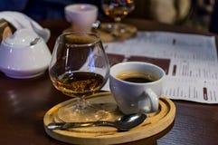 咖啡用科涅克白兰地,在桌上 免版税库存照片
