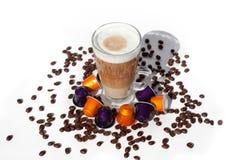 咖啡胶囊不同颜色、咖啡豆和白色杯子与奶油色牛奶泡沫的热的咖啡在被隔绝的白色背景 免版税库存图片