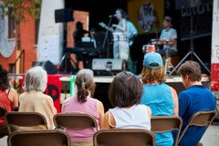 Åhörarna håller ögonen på en lokal jazzbandkonsert på en utomhus- etapp royaltyfri fotografi
