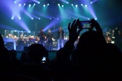 Åhörarna på en konsert på bakgrunden av platsen. Royaltyfria Foton