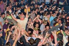 Åhörarna som gör att surfa för folkmassa (också som är bekant som, mosh gropen) Arkivfoto