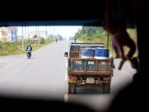 Åka lastbil den bärande metallbehållaren som kör längs en slät och nästan tom gata Royaltyfri Fotografi