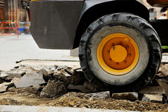 Åka lastbil gummihjulet på en bruten asfalt på konstruktionsplatsen i stads- env Fotografering för Bildbyråer