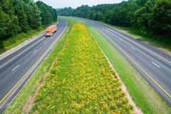 Åka lastbil körning på den gula blomman fodrade statliga huvudvägen i lantliga Virginia Arkivbilder