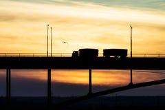 Åka lastbil körning på en bro på en bakgrund av en härlig himmel Arkivfoto