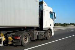 Åka lastbil med behållaren på vägen, sidosikt med klart tomt utrymme Royaltyfri Fotografi