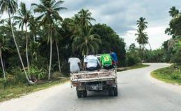 Åka lastbil med folk på bakgrunden som kör på den afrikanska vägen Arkivfoto