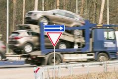 Åka lastbil med nya bilar på vägen med vägmärket Arkivbild