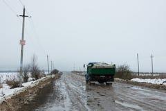 Åka lastbil på den durty vägen med gropar och pölar Arkivbilder