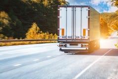 Åka lastbil på den lantliga vägen för asfalt på solnedgången Royaltyfri Fotografi