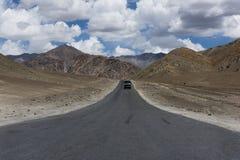 Åka lastbil på en rak väg i bergterräng Royaltyfria Bilder