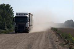 Åka lastbil på grusvägen med damm bak det bygd Royaltyfria Bilder