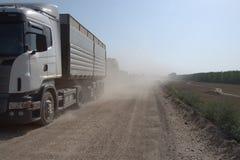 Åka lastbil på grusvägen med damm bak det bygd Arkivbild