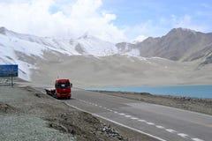 Åka lastbil på huvudvägen på Bulunkou och turkosblått för sjön, för dyn för sand vatten på på den Karakoram huvudvägen, Xinjiang arkivfoto