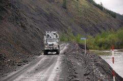 Åka lastbil på vildmark Ryssland för den grusvägKolyma huvudvägen Arkivbilder