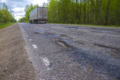 Åka lastbil rörande på en bruten väg med gropar Royaltyfri Bild