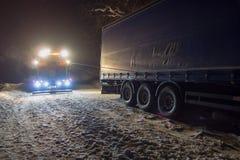 Åka lastbil trafikolyckan på natten, på en snöig vinterväg Den starkt upplysta sabotörlastbilen drar en lastbil ut ur att hänga f Arkivbilder