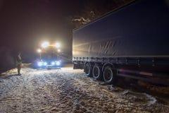 Åka lastbil trafikolyckan på natten, på en snöig vinterväg Den starkt upplysta sabotörlastbilen drar en lastbil ut ur att hänga f Royaltyfri Foto