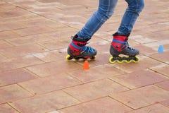 Åka skridskor i-linjen i gatan med kottar Arkivbild