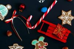 Åka släde med gåvan, julkakor, godis på en mörk bakgrund Arkivfoton