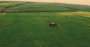 Åkerbruk traktor som besprutar fältet för sommarskördvete lager videofilmer