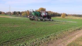 Åkerbruk traktor som besprutar skördfältet arkivfilmer