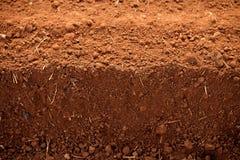 åkerbruka lerafält plöjde red smutsar Royaltyfri Foto