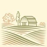 Åkerbrukt landskap med ladugården och träd Arkivbild