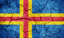 Åland Islands flag. On dry earth ground texture background Royalty Free Stock Photo