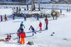 Åldersgrupper för folk som allra tycker om solig dag, åker skridskor och spelar ishockey på en djupfryst sjö, när temperaturer ta royaltyfri fotografi