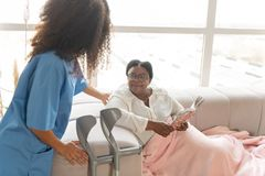 Åldrades kvinnan som den har, vilar på soffan och att se att bry sig sjuksköterskan royaltyfri fotografi