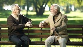 Åldrades manliga vänner med gå pinnar som vilar på bänk parkerar in, och samtal royaltyfria bilder