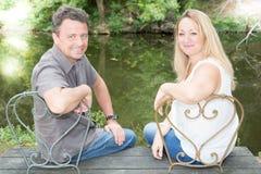 Åldrades par för Forties sitter mitt på gummilackaflodbänk arkivbilder