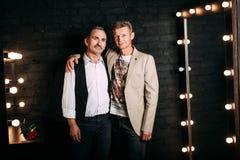 Åldrades stilig mitt två män, en är iklädd en vit skjorta, och en svart väst, annan bär omslaget, gamla vänner Svart bakgrund royaltyfria bilder
