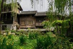 Åldrades tegelplatta-taklade trähus bak trädgård i solig vår royaltyfria bilder