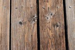 Åldrades träplankor spikade till en strandpromenad arkivfoton