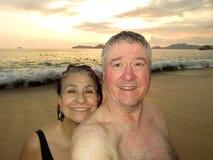 Åldrats mellersta kopplar ihop på solnedgången i Acapulco arkivbild
