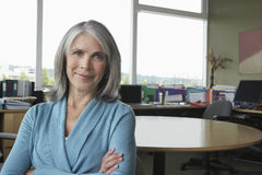 Åldrig affärskvinna Smiling At Office för mitt royaltyfri fotografi